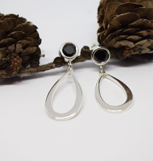 droppformade silverörhängen med svart sten på vit bakgrund med kottar bakom