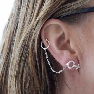 silversmycken i form av kvinnosymbolen på öra på kvinna