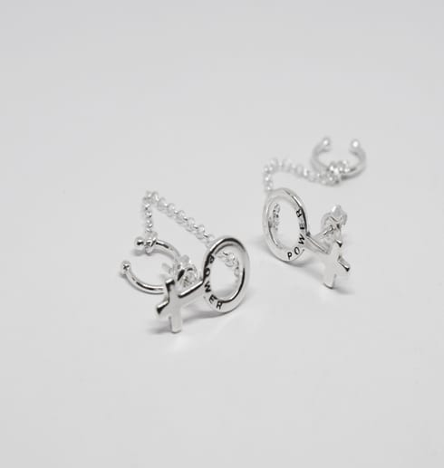 silverörhängen i form av kvinnosymbolen på vit botten