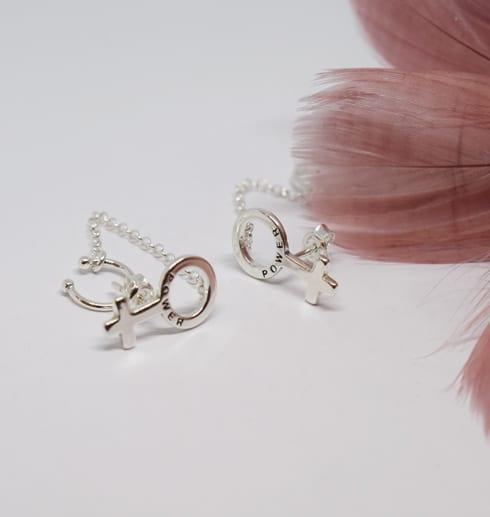 silverörhängen i form av kvinnosymbolenpå vit bakgrund med rosa fjäder bredvid