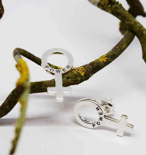 silverörhängen i form av kvinnosymbolen på trädgren