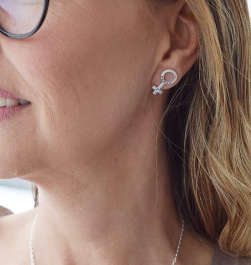 silverörhängen i form av kvinnosymbolen på kvinna utomhus