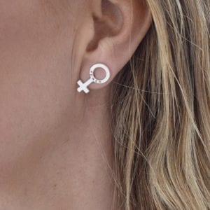 silverörhängen i form av kvinnosymbolen på öra på kvinna utomhus