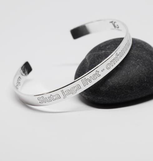 silverarmband med text på svart sten med vit bakgrund