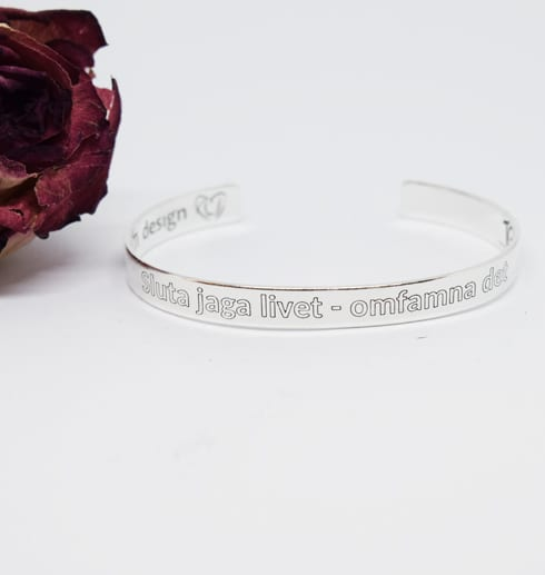 silverarmband med text på vit bakgrund med ros bredvid