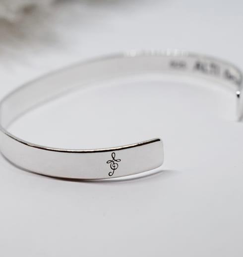 silverarmband med text på vit botten med strutsfjäder bredvid