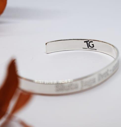 silverarmband med text på vit botten med orange kvist