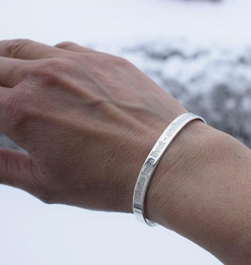 silverarmband med text på kvinnas arm utomhus