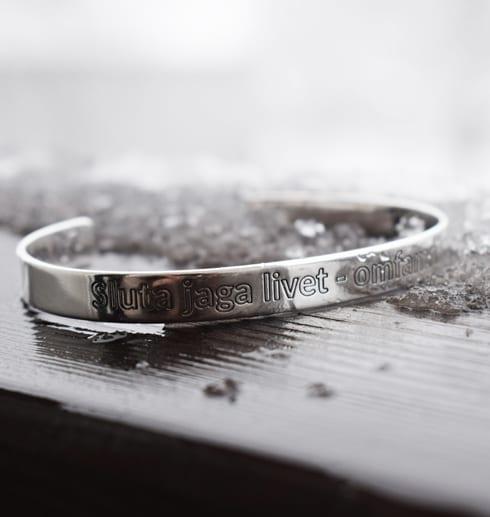 silverarmband med text på träräcke med snö utomhus