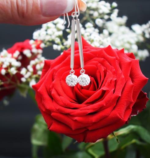 silverörhängen med swarowskikristaller mot röd ros och vita småblommor utomhus