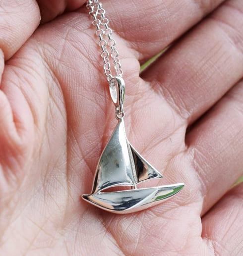 segelbåt i silver i handflata utomhus