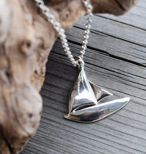 silverhalsband i form av en segelbåt på trä med trädgren bredvid utomhus