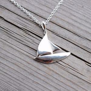 silverhalsband i form av en segelbåt på trä utomhus