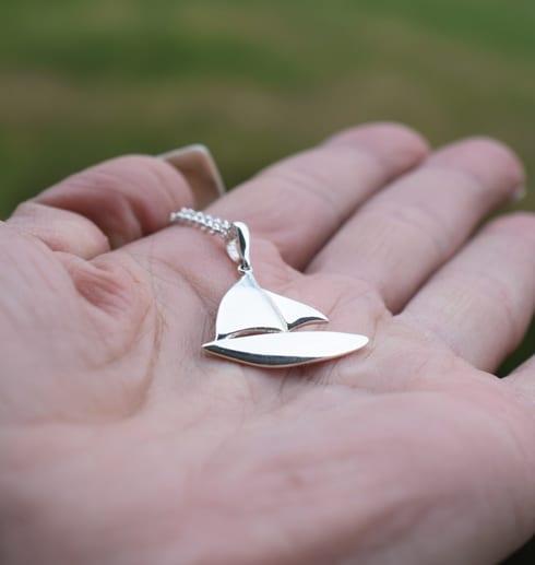 silverhalsband i form av en segelbåt i handflata utomhus