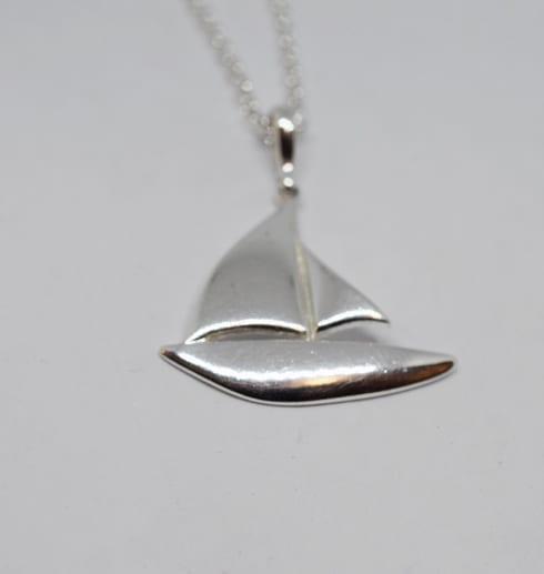 halsband i form av en segelbåt i silver mot vit bakgrund