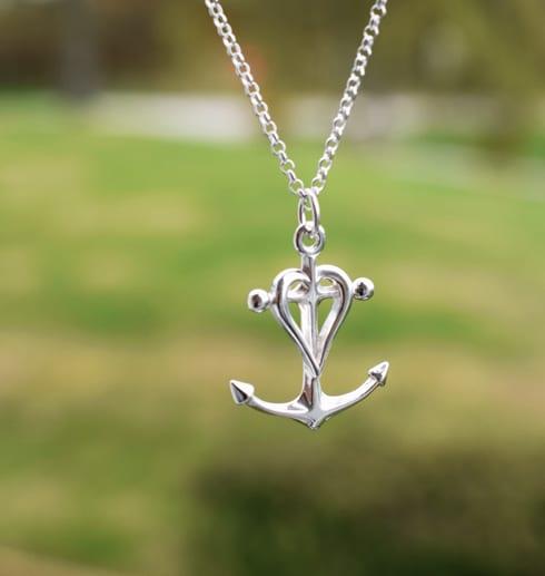 silversmycke i form av ett ankare, hjärta och kors hängande i luften utomhus med grön bakgrund