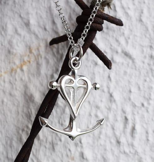 silverhalsband i form av ett ankare, kors och hjärta utomhus på rostig taggtråd