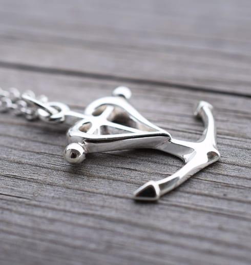 silversmycke i form av ett ankare, hjäta och kors på trä utomhus