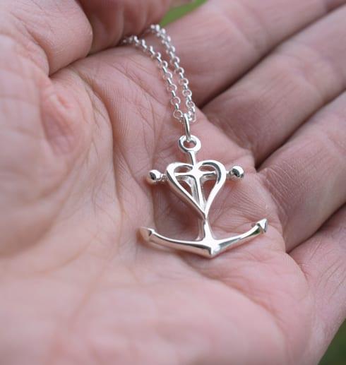 silversmycke i form av kors, ankare och hjärta i handflata utomhus