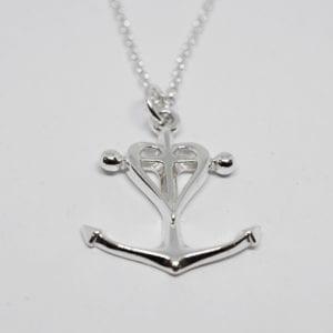 Silversmycke i form av tro, hopp och kärlek på vit bakgrund