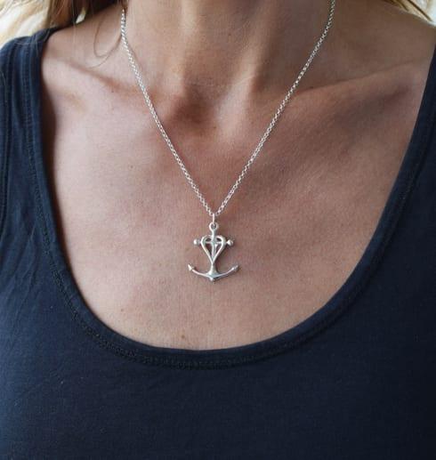 silverhalsband i form av ett kors, ett ankare och ett hjärta runt halsen på en kvinna utomhus