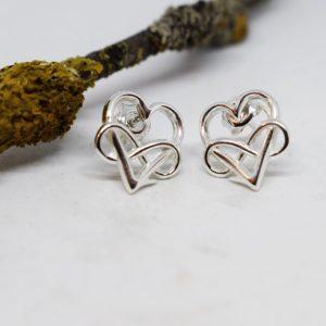 silverörhängen i form av ett hjärta med en evighetssymbol