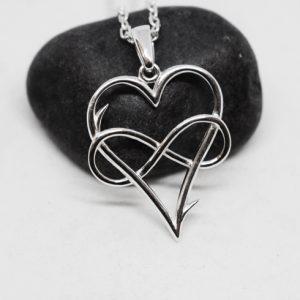 silverhjärta med evighetssymbol på svart sten