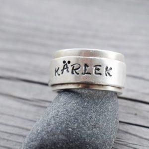 bred silverring med texten KÄRLEK på grå sten med trä bakom utomhus