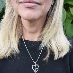silverhalsband i form av ett dubbelhjärta på kvinna med svart tröja