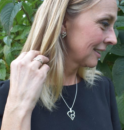 Silverhalsband i form av ett dubbelhjärta på kvinna utomhus i svart tröja