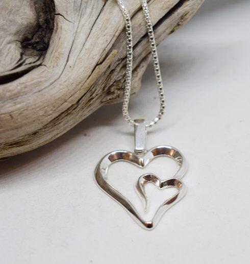 Silverhalsband i form av ett dubbelhjärta på vit botten med trädgren