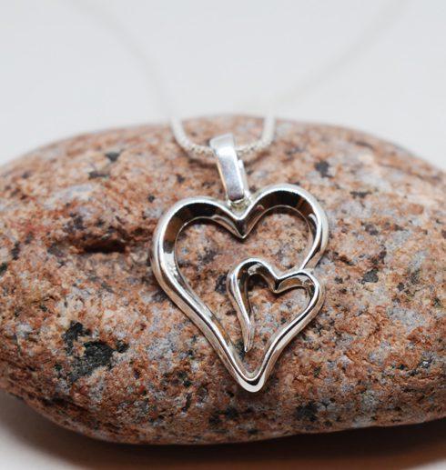 Silverhalsband i form av ett dubbelhjärta på röd sten