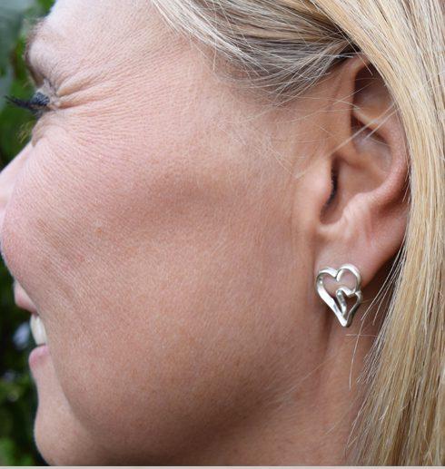 silverörhängen i form av hjärtan på kvinnas öra
