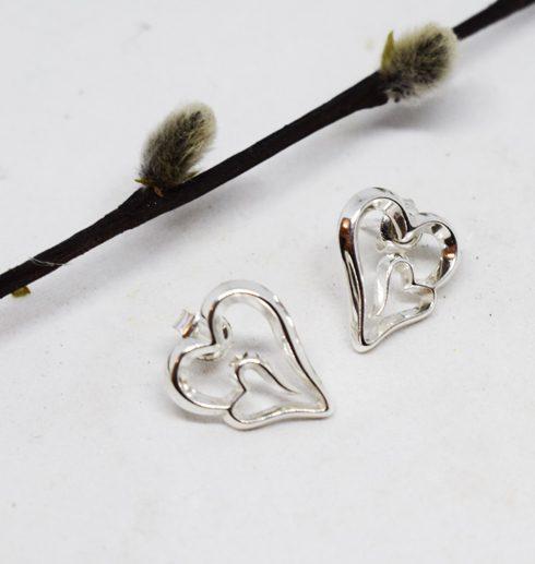 silverörhängen i form av hjärtan på vit botten med videkisse bakom