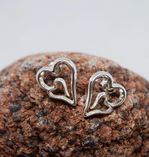 silverörhängen i form av hjärtan på röd sten