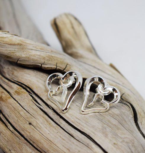 silverörhängen i form av hjärtan på trädgren