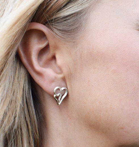 silverörhänge i form av hjärtan på kvinnas öra