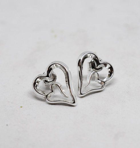 silverörhängen i fom av hjärtan på vit bakgrund
