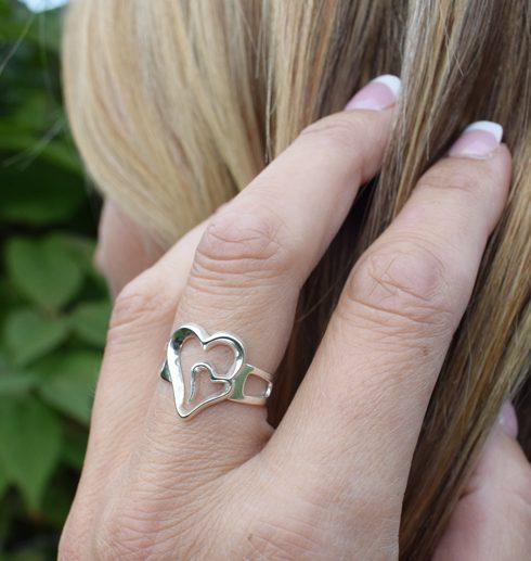 silverring med dubbelhjärta på kvinnas finger utomhus
