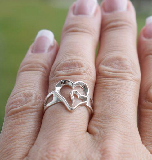 Silverring i form av ett dubbelhjärta på finger