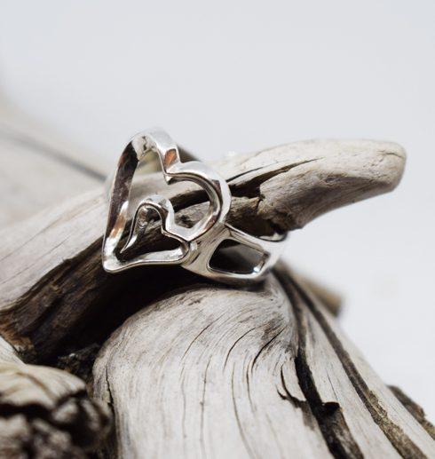 silverring i form av dubbelhjärta på trädgren