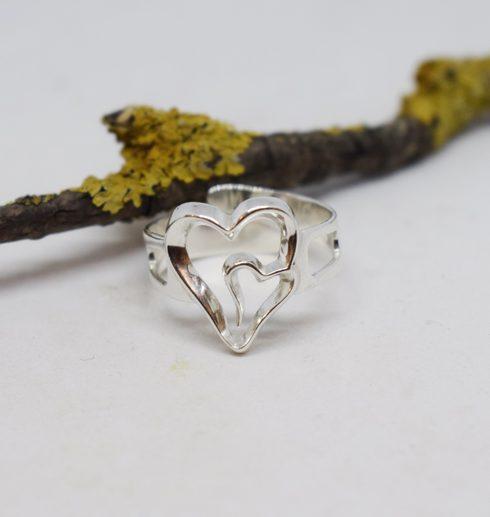 silverring med dubbelhjärta på vit bakgrund med gren i bakgrunden