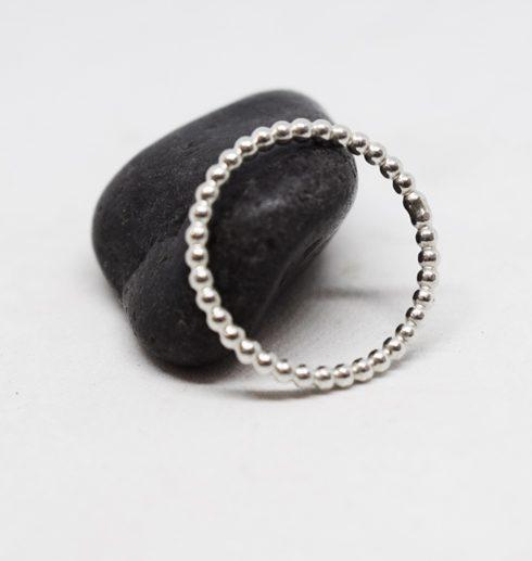 silverring i kultråd mot svart sten och vit bakgrund