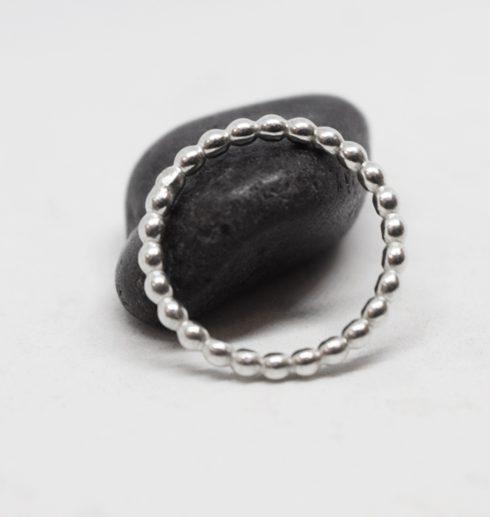 kultrådsring i silver som lutar sig mot svart sten med vit bakgrund