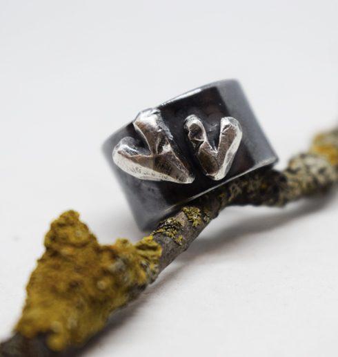 svartoxiderad silverring med två hjärtan på träpinne
