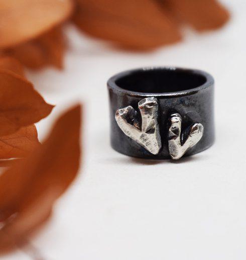 svartoxiderad silverring med hjärtan på vit botten med orange löv bredvid