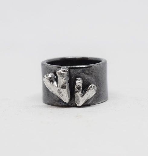 svartoxiderad silverring med hjärtan på vit bakgrund