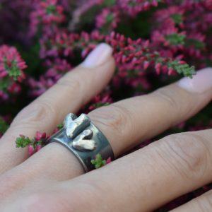 svartoxiderad silverring med hjärtan på finger med ljung utomhus